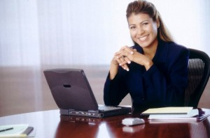 Young financial analyst at a computer, she is happy in her job, smiling