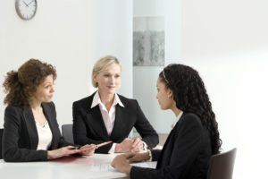 three ladies, an HR manager, CFO, and a job applicant, talk together in a nice white office.